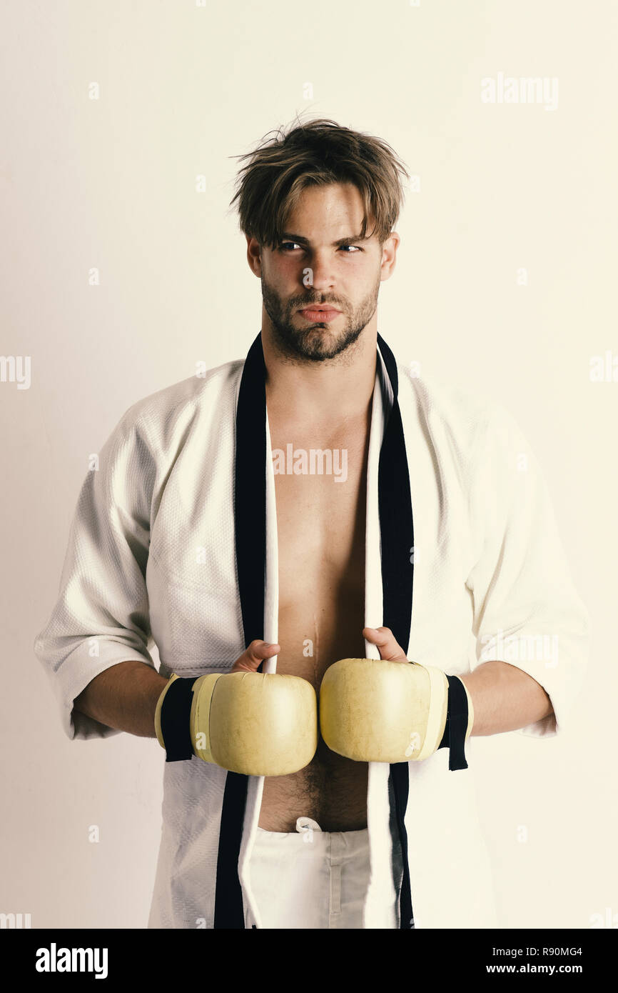 MMA fighter with strong body practices martial arts. Man with tricky face and bristle on white background. Mixed martial arts training concept. Guy poses in white kimono wearing golden boxing gloves - Stock Image