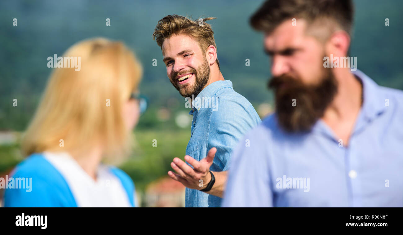 Man with beard jealous aggressive because girlfriend interested in handsome passerby. Husband strictly watching his wife looking at another guy while walk. Passerby smiling to lady. Jealous concept. - Stock Image