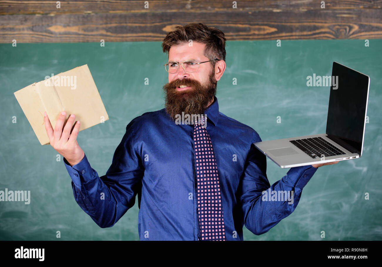 Digital against paper. Choose right teaching method. Teacher choosing modern teaching approach. Teacher bearded hipster holds book and laptop. Modern technologies benefit. Modern instead outdated. - Stock Image