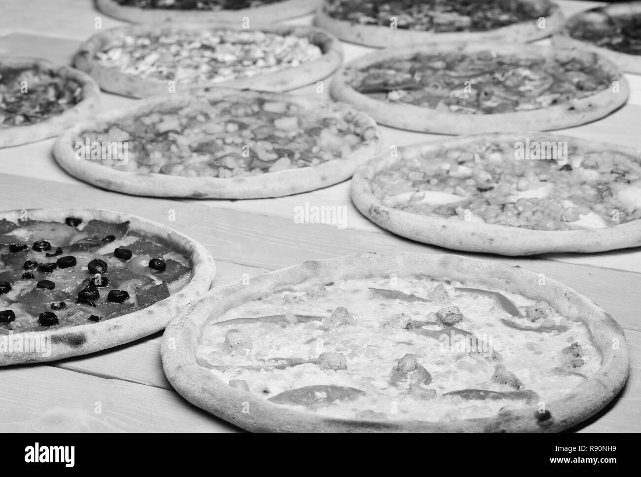 Pizza circles with meat, mushrooms, tomatoes and cheese on wooden background. Take away food with various ingredients and crunchy edges. Different pizza set for menu. Fast food restaurant concept - Stock Image