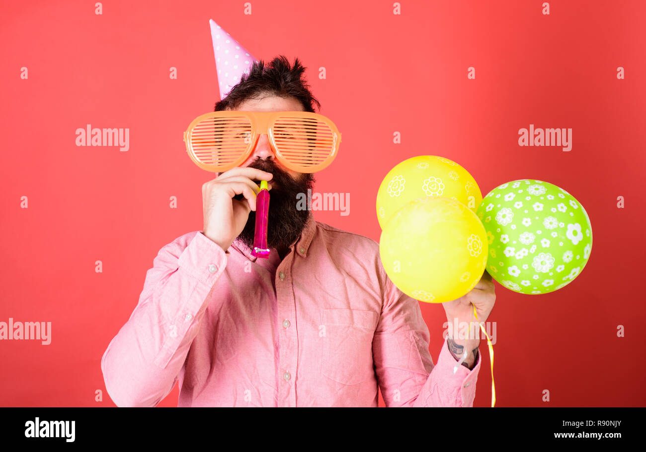 Man with beard on calm face with party horn and air balloons, red background. Guy in party hat with holiday attributes celebrates. Surprise concept. Hipster in giant glasses blows into party horn. - Stock Image