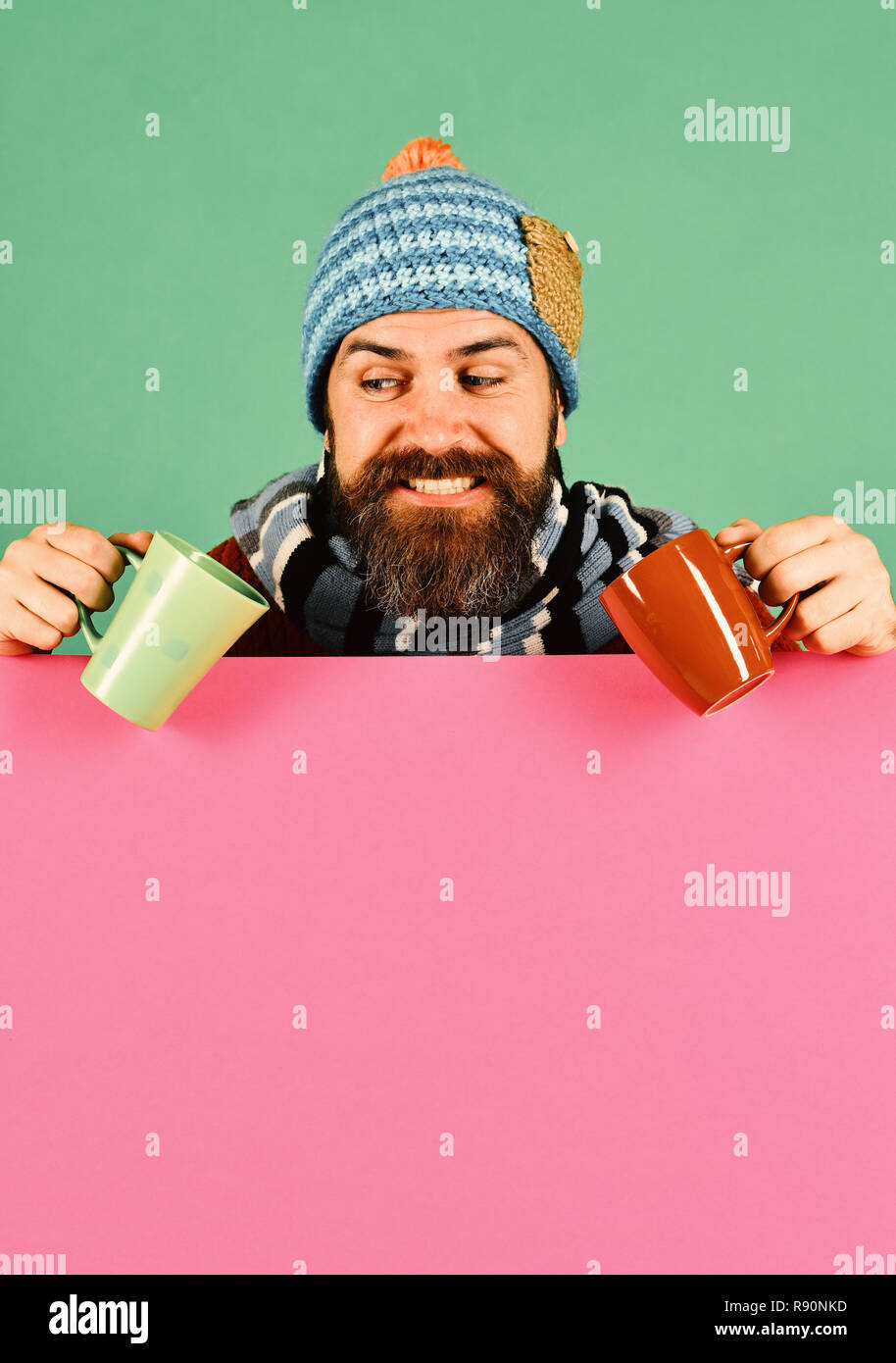 Man with beard holds brown and green cups of tea. Guy with tricky smile wears warm hat on green and pink background, copy space. Fall season and warm beverage time. Hot drinks and autumn concept - Stock Image