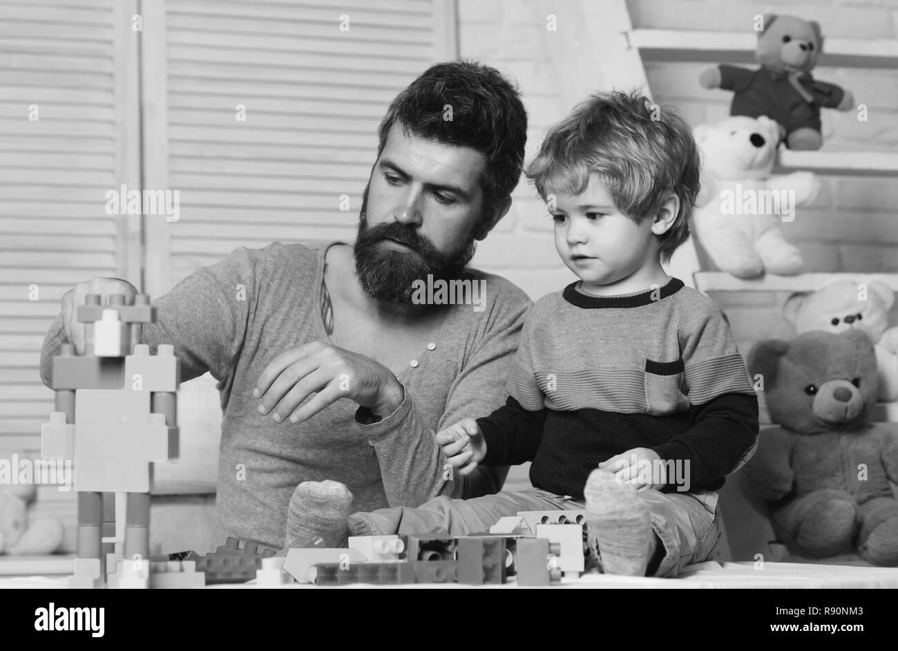 Boy and bearded man play together on wooden background. Father and son with busy faces create colorful constructions with toy bricks. Family and childhood concept. Dad and kid build of plastic blocks - Stock Image