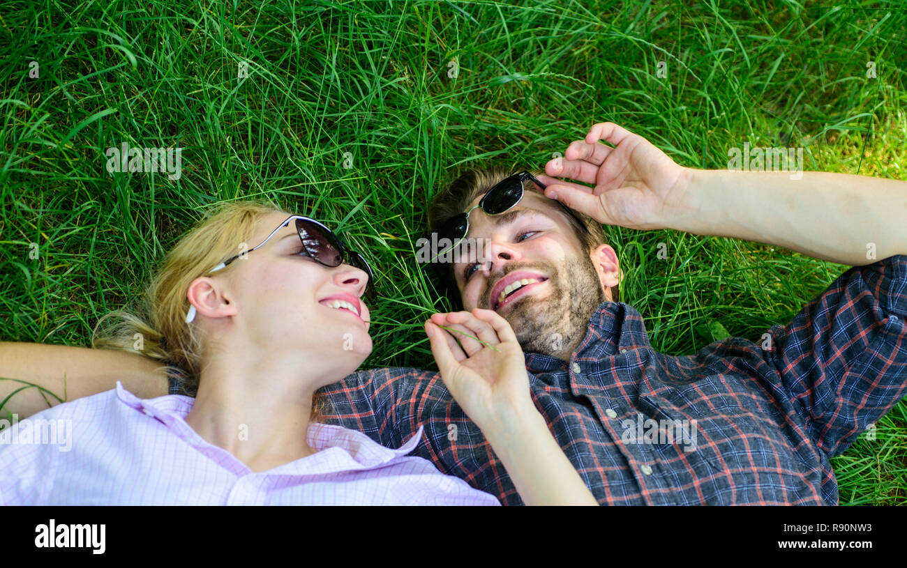 Couple in love united with nature. Nature fills them with freshness and inspiration. Man unshaven and girl lay on grass meadow. Guy and girl happy carefree enjoy freshness of grass. Closer to nature. - Stock Image