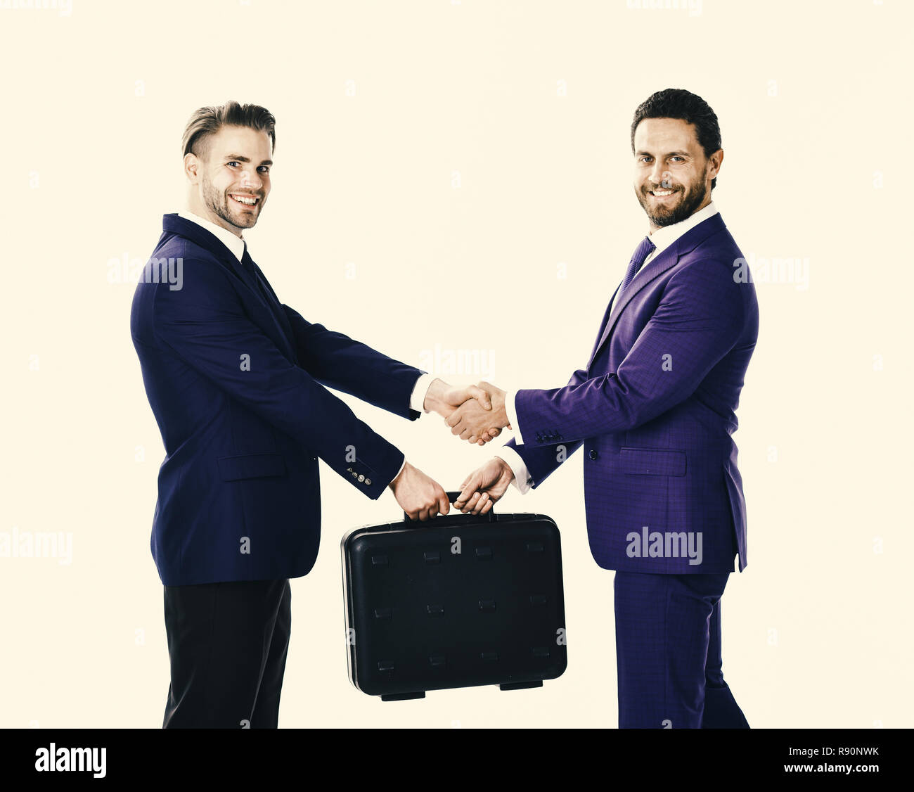 Handover of suitcase in hands of partners on white background. Businessmen with happy faces shaking hands and hold briefcase. Business exchange between businessmen in suits. Successful deal concept. - Stock Image