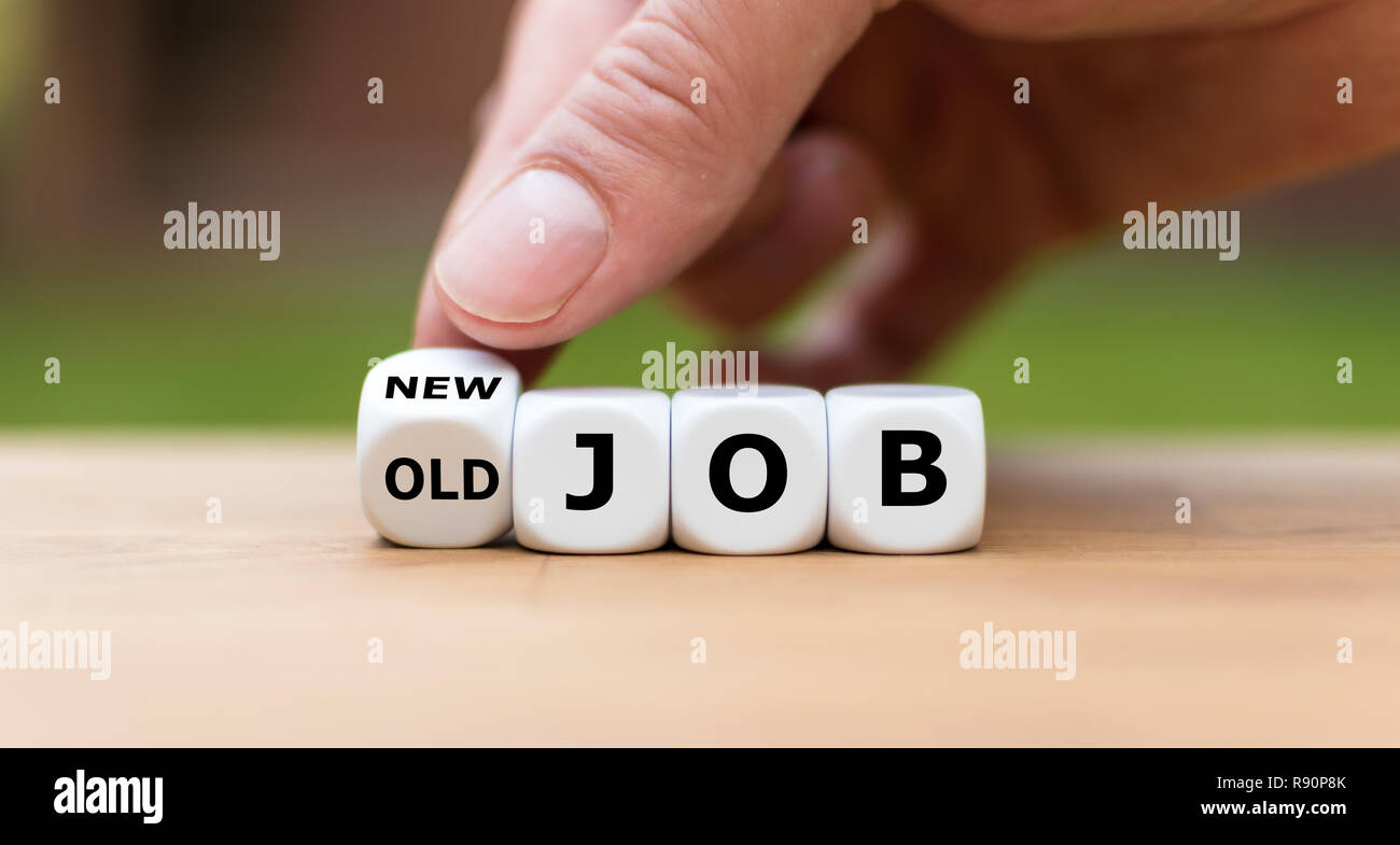 "Hand is turning a dice and changes the expression ""old job"" to ""new job"" Stock Photo"
