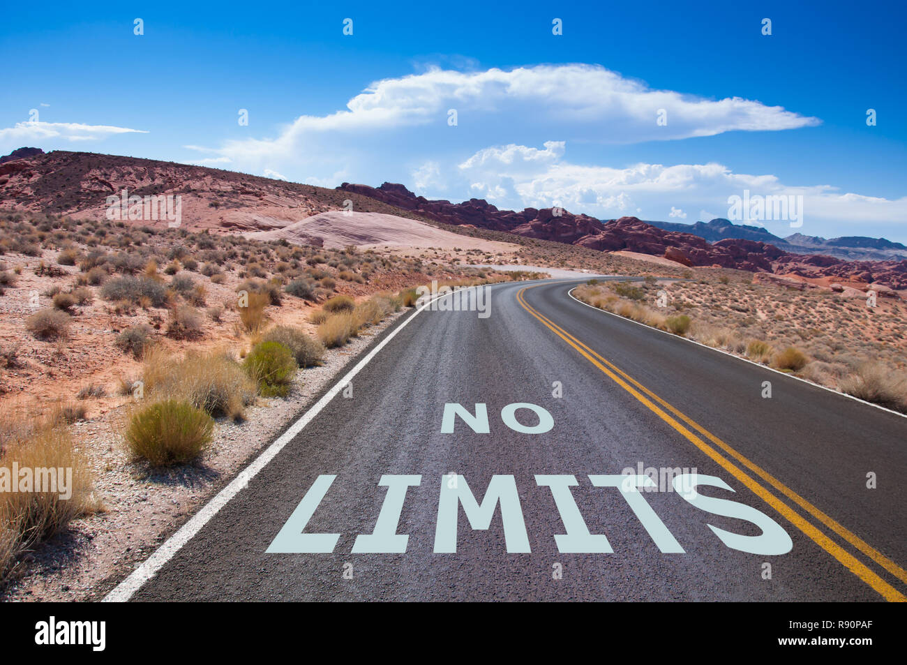 """The text """"NO LIMITS"""" written on a empty road in the desert of Nevada before the street turns right Stock Photo"""