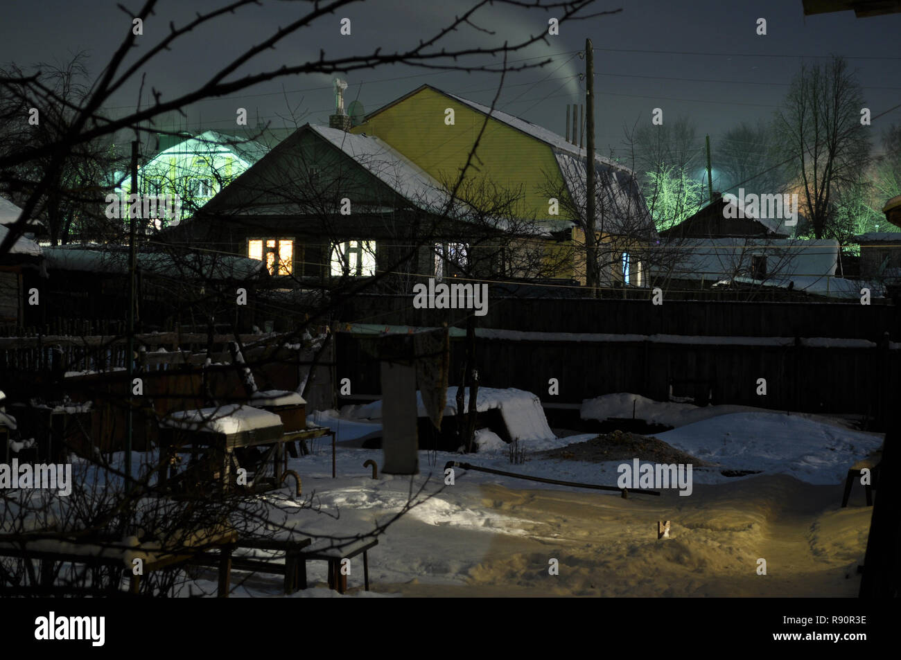 Kovrov, Russia. 24 January 2010. Courtyard of single storey old wooden house in the late evening - Stock Image