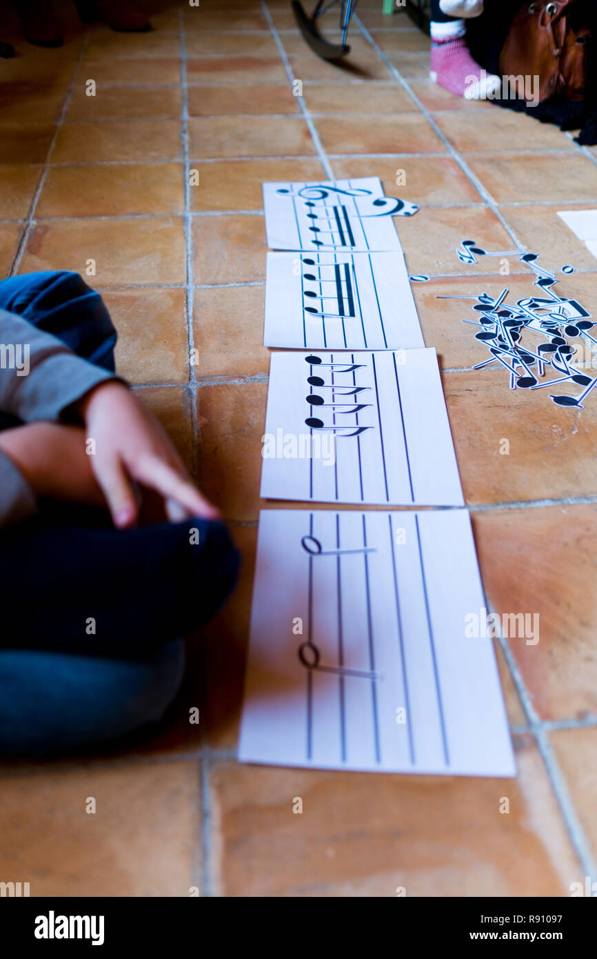 cropped view of an eleven year old boys' hands composing music with cut out musical notes on a music score sheet on a terracotta tiled floor - Stock Image