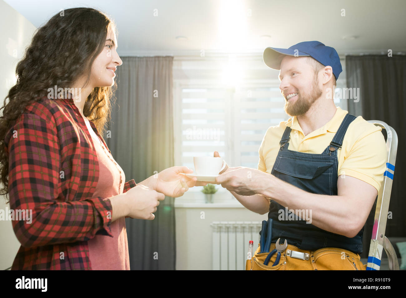 Hospitable lady giving coffee to repairman Stock Photo
