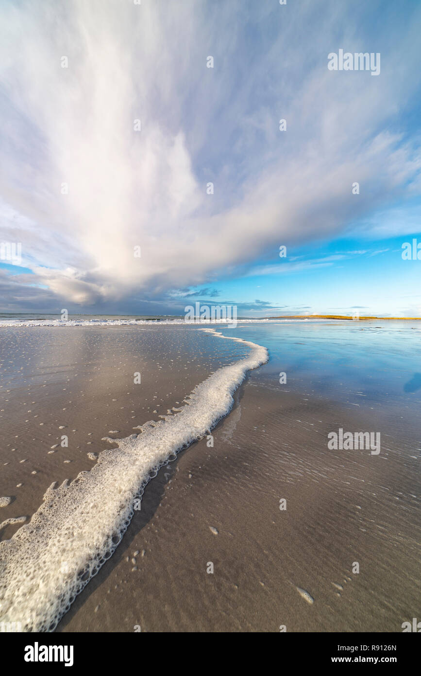 Wide angle shot of the ebb and flow of the sea with dramatic skies on Outer Hebrides beach, Scotland - Stock Image