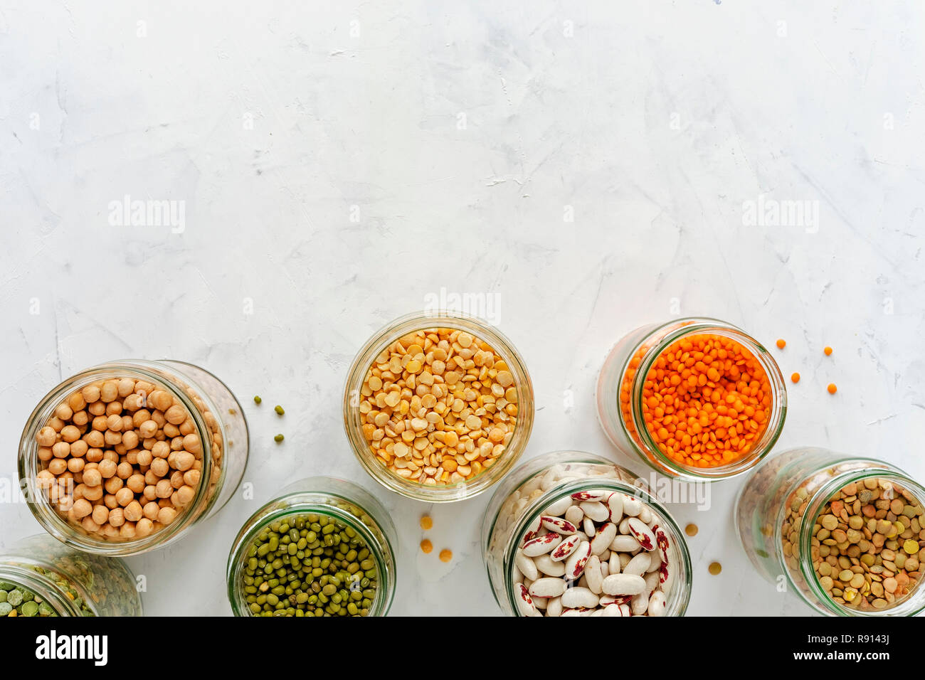 Open glass jars full of assorted dried legumes with mung beans, beans, lentils and peas over a white background in a healthy diet and nutrition concep Stock Photo