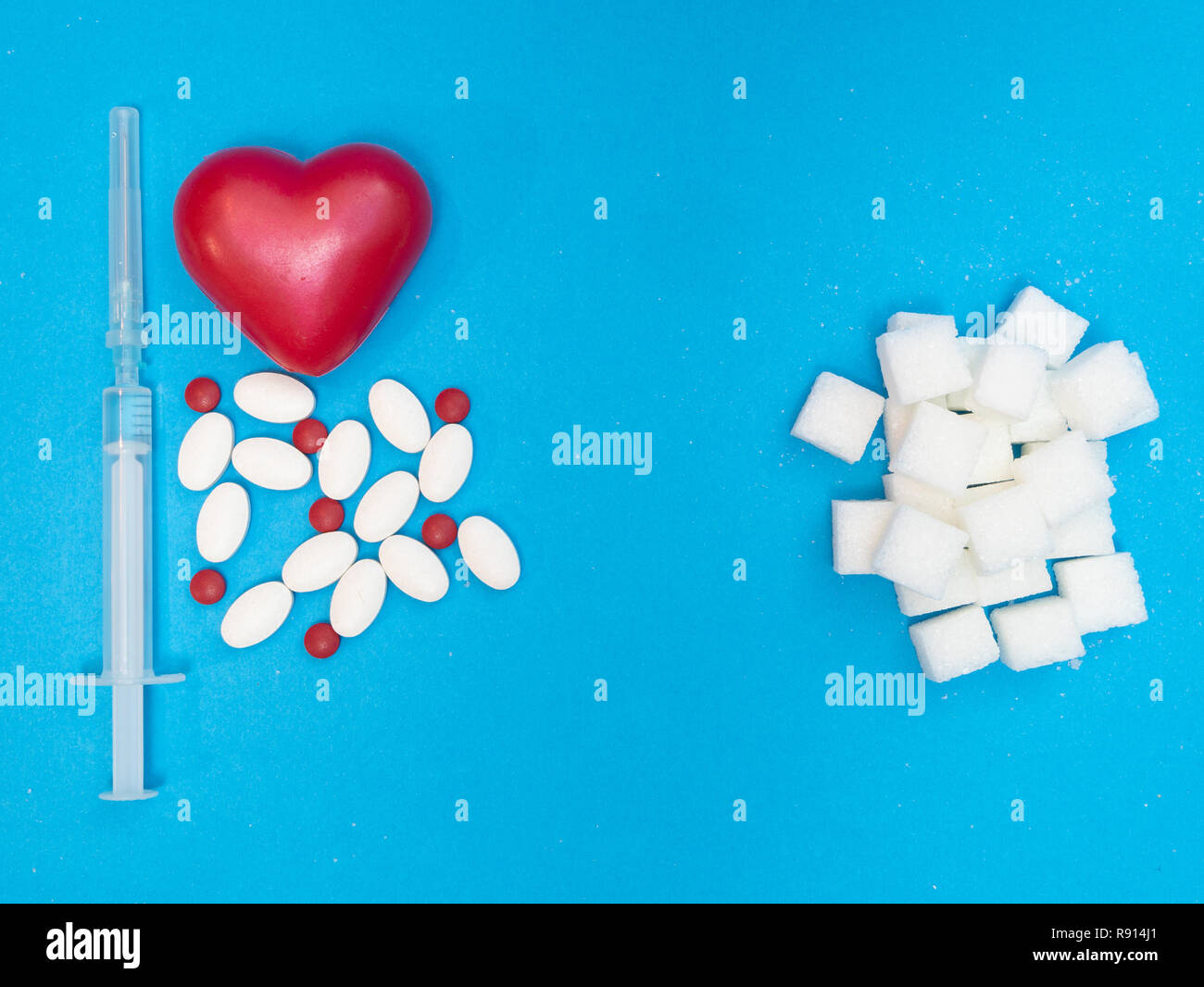 high level of sugar in blood cause heart disease. pills, drugs, red heart and syringe of injection and white blocks of refined sugar on blue backgroun - Stock Image