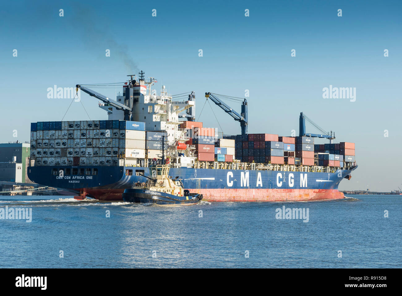 Shipping on the Thames.  The CMA CGM Africa One container ship accompanied by the tug Svitzer Brunel steaming downriver on the River Thames. Stock Photo