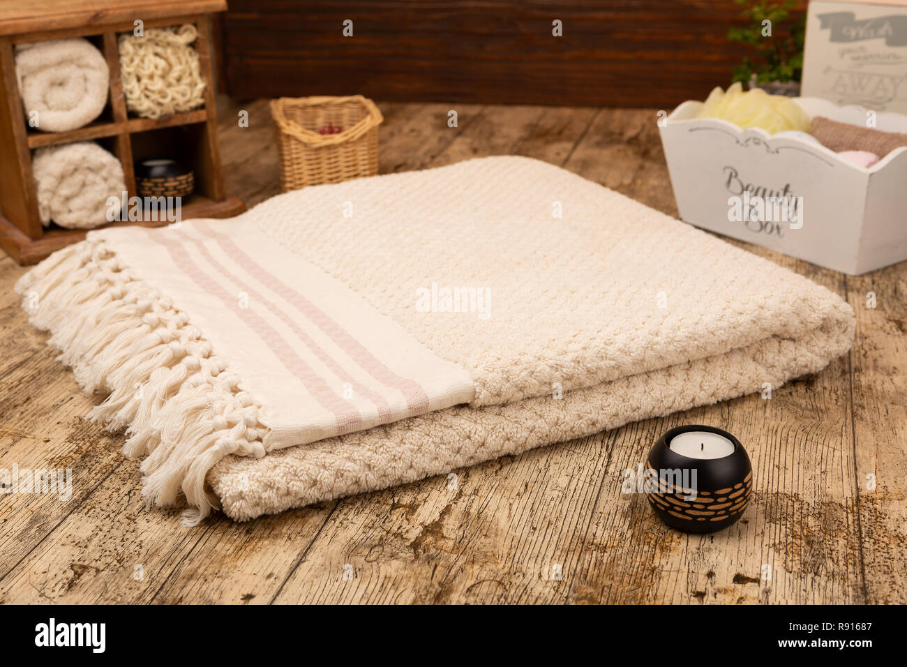 Large handwoven cotton bath towel on wooden background surrounded by bathroom props - Stock Image
