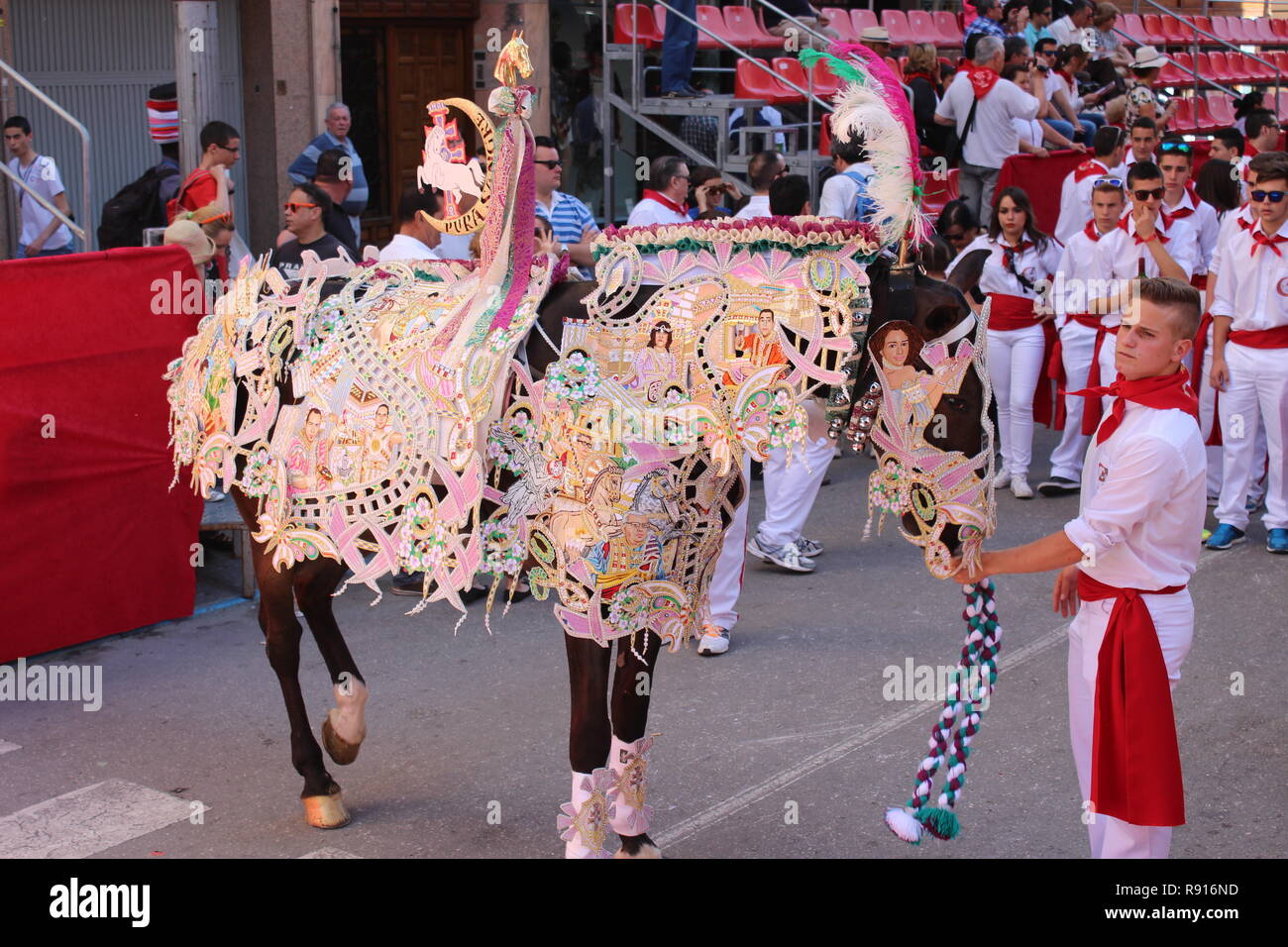 Boy with a horse in embroidered costume in the parade at Los Caballos Del Vino Caravaca de la Cruz.  Embroidery is used to make the horse costume - Stock Image