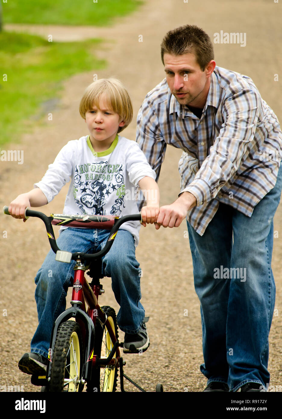 An autistic boy gets help from his father as he rides his bicycle up a steep hill, April 21, 2012, in New Hope, Mississippi. - Stock Image