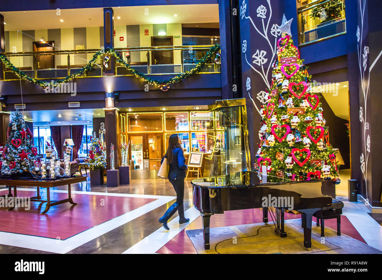 Andorra la Vieja, Andorra - Dec 10th 2017 - Young woman walking in the decorated interior near a christmas tree of the Plaza Hotel in Andorra La Vieja Stock Photo