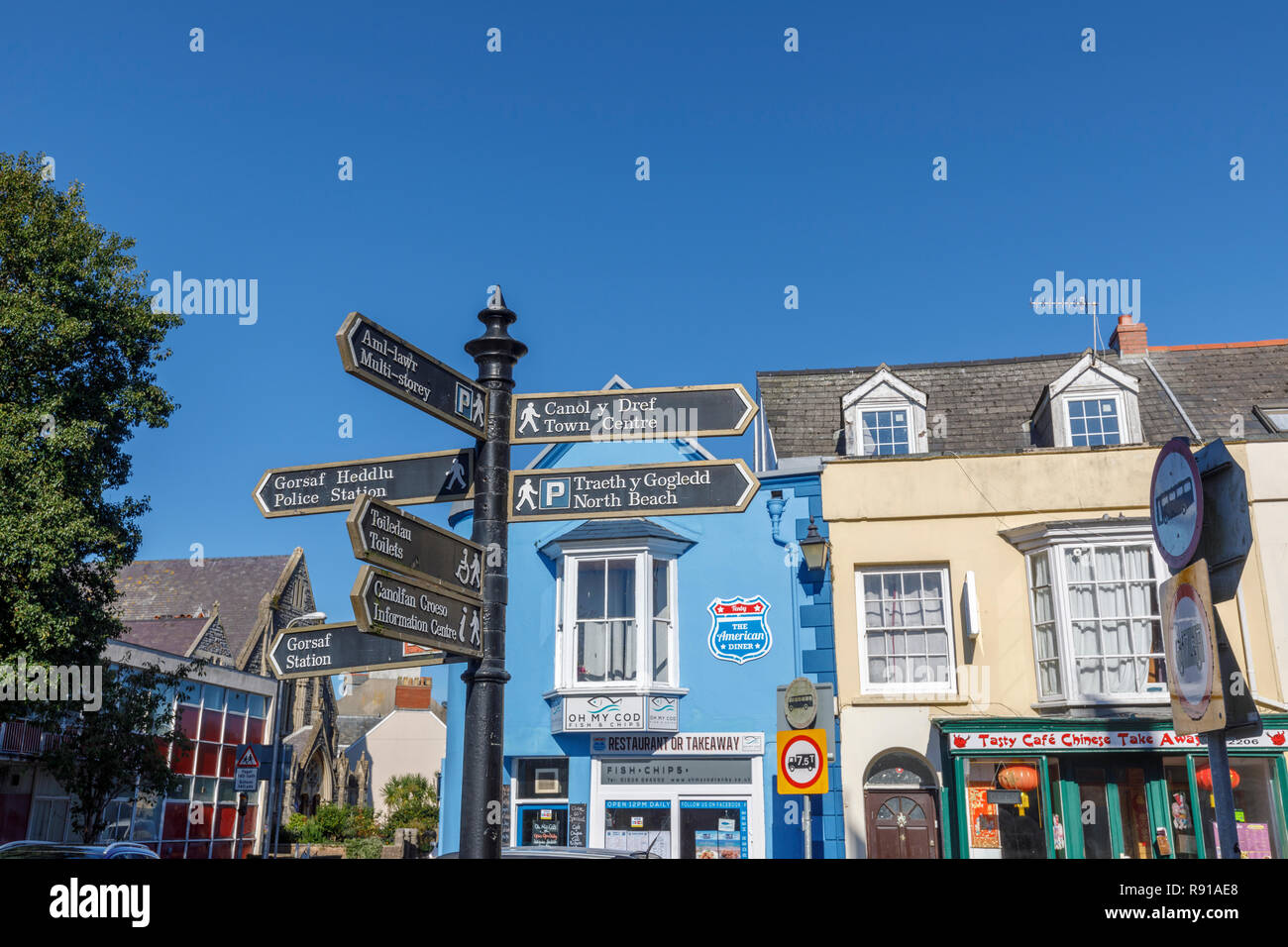 Signpost in the centre of Tenby, a walled seaside town in Pembrokeshire, south Wales coast on the western side of Carmarthen Bay - Stock Image