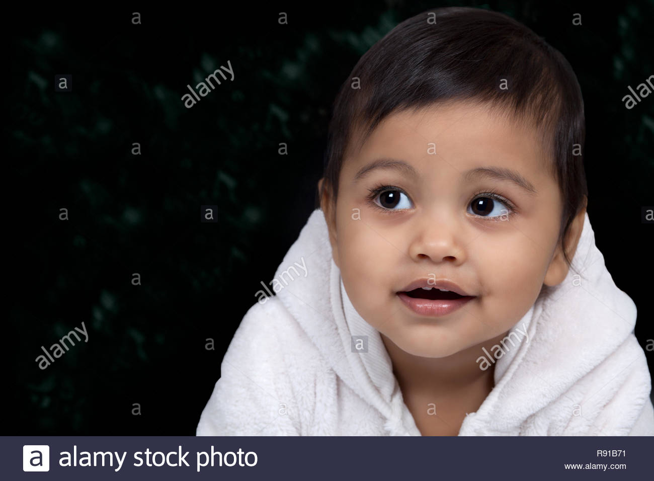 Cute baby face portrait, on dark background with copy space - Stock Image