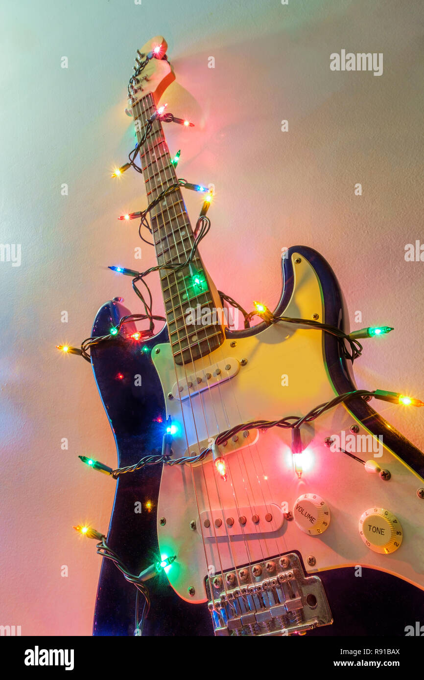 3b6127571a79b Seasonal holiday musical instrument electric guitar wrapped in Christmas  tree string lights
