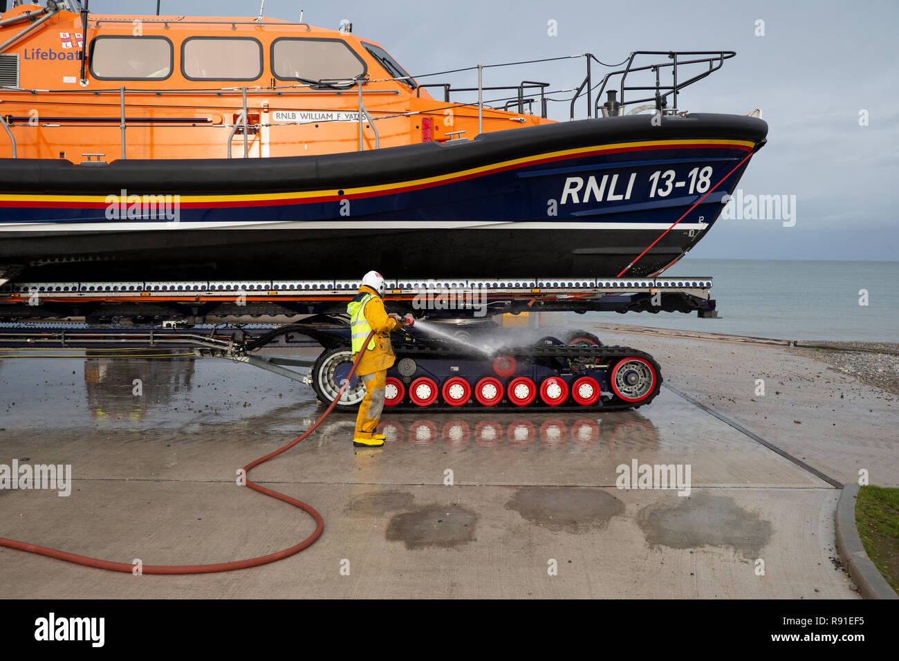 A Llandudno RNLI lifeboat crew member hosing down the tractor gear on the William F Yates Shannon Class lifeboat following sea exercises - Stock Image