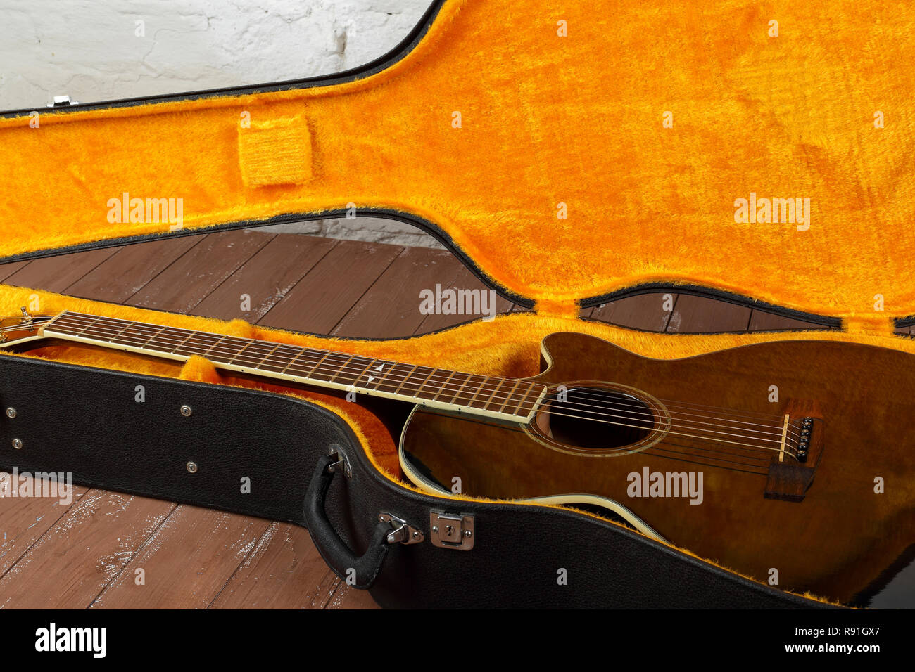 Musical instrument - Fragment brown cutaway acoustic guitar in hard case on a wood background. Stock Photo