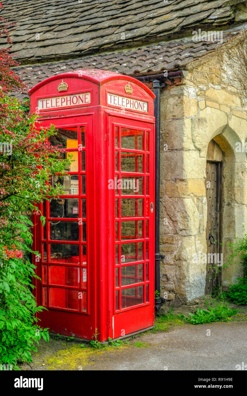 A red telephone box in the picturesque village of Castle Combe, Wiltshire, England, Europe. - Stock Image