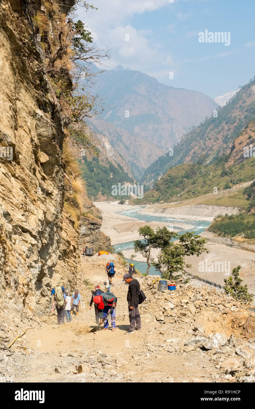 Trekkers on the Manaslu Circuit trek in Nepal walking through a section of new road under constructuion - Stock Image