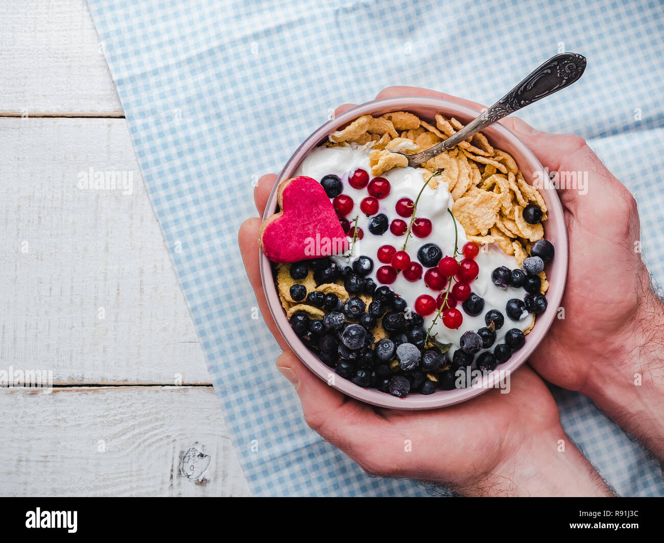 Festive and Healthy breakfast for loved ones. Cereal biscuits in pink glaze, cornflakes, yogurt, fresh berries on the background of white boards. Clos Stock Photo