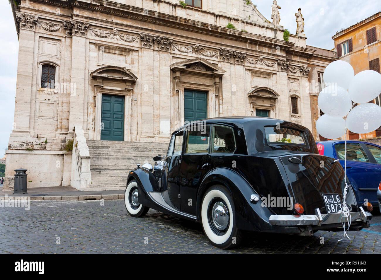 Old black limousine waits for wedding couple at front door of Santa Maria della Consolazione church, Rome, Lazio, Italy - Stock Image