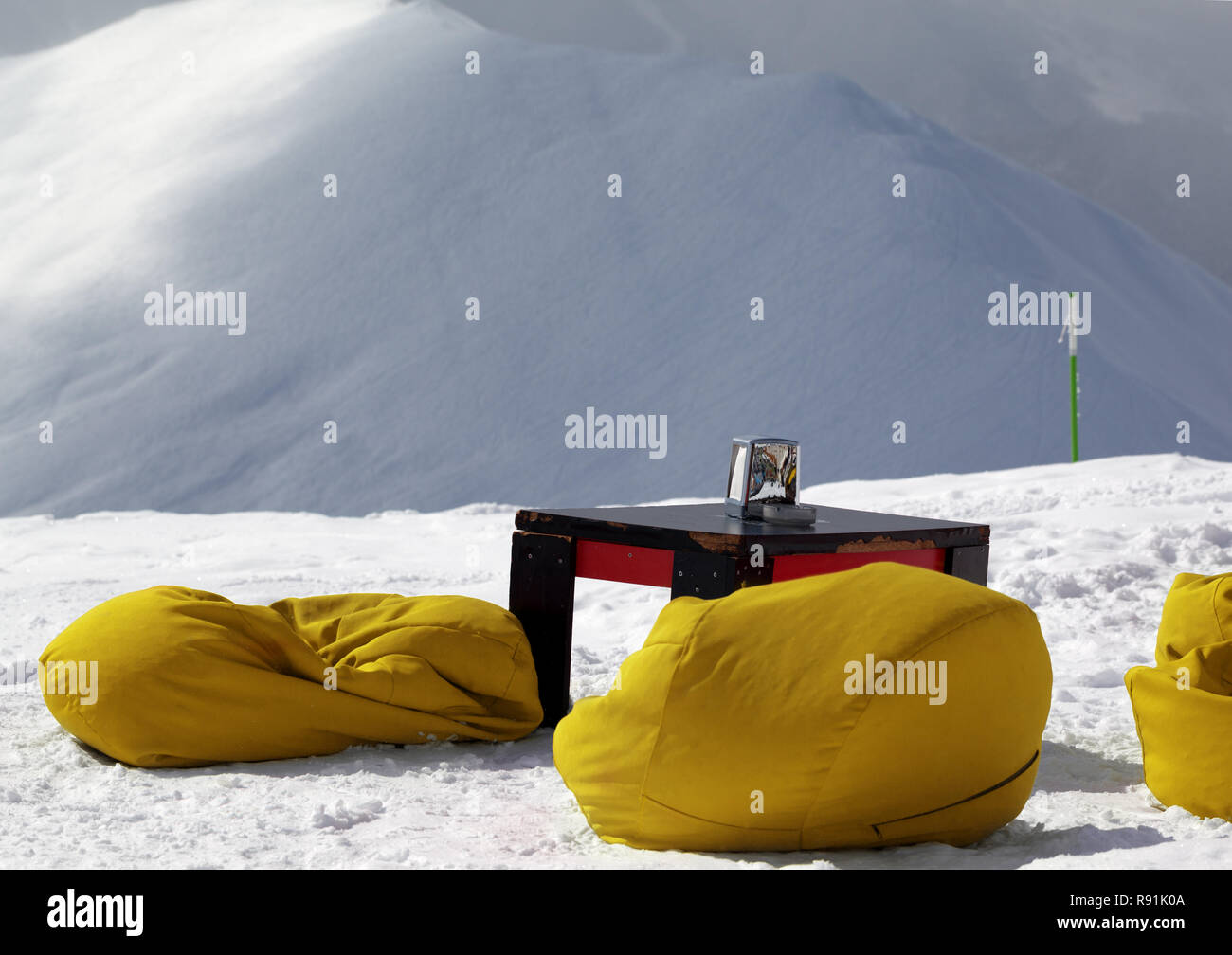 Yellow bean bag chairs and old table in outdoor cafe at ski resort and snow slope for freeriding at background in winter sun day. - Stock Image