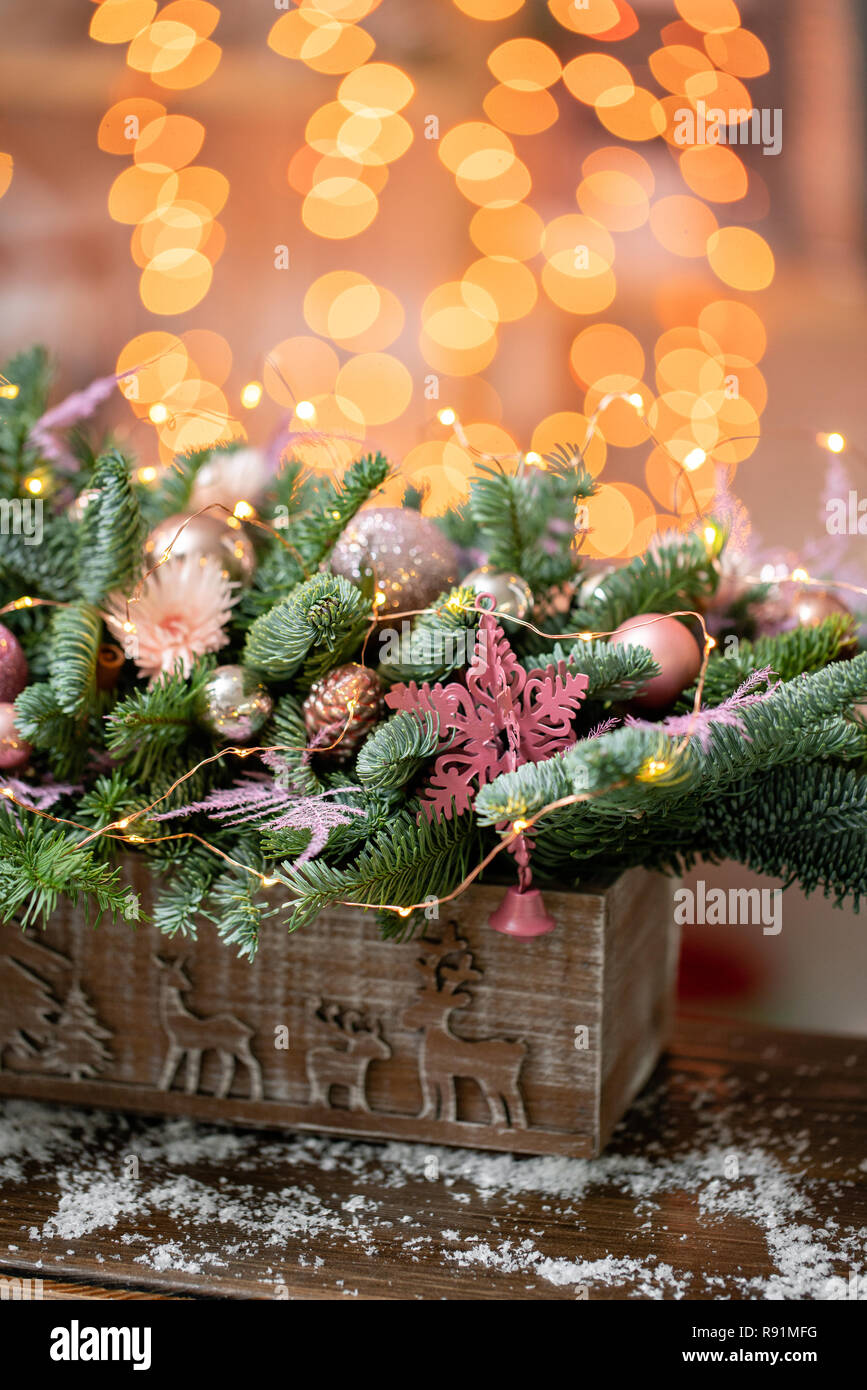 Beautiful festive arrangement of fresh spruce, pink ornamentals in a rustic wooden box box. Christmas mood. Garland bokeh on background. - Stock Image