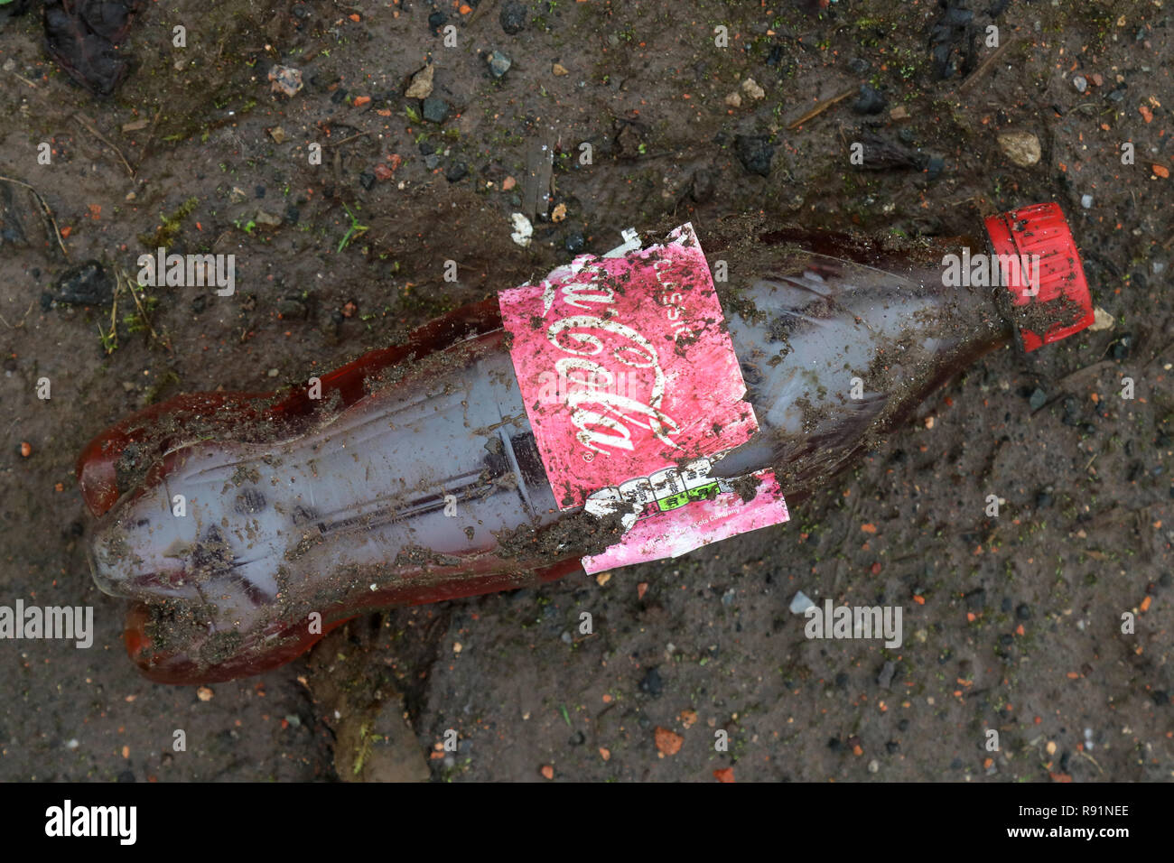 A dirty discarded plastic Coca Cola bottle in the mud at the former IBM factory site in Spango Valley, Greenock, Scotland - Stock Image
