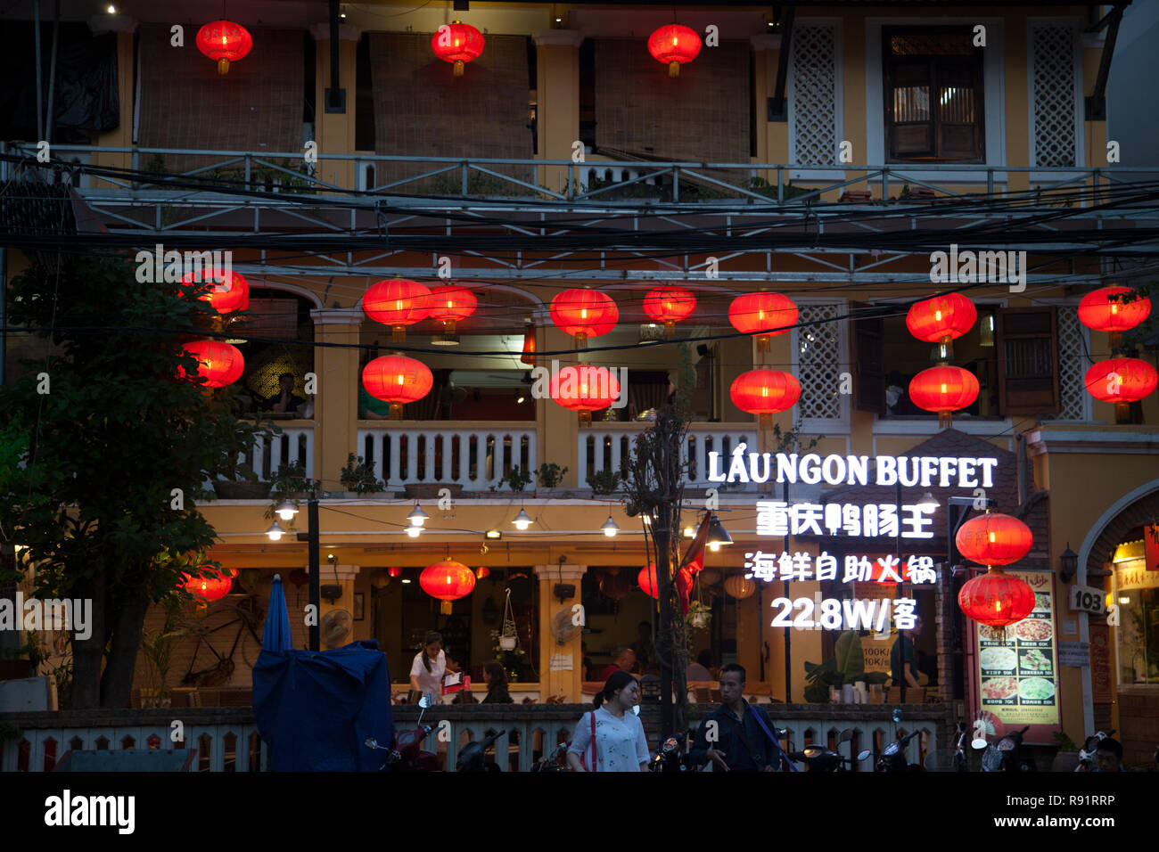 Nha Trang, Vietnam: Asian restaurant exterior decorated with red paper lanterns. People eating at a Chinese buffet, view of windows from outside Stock Photo