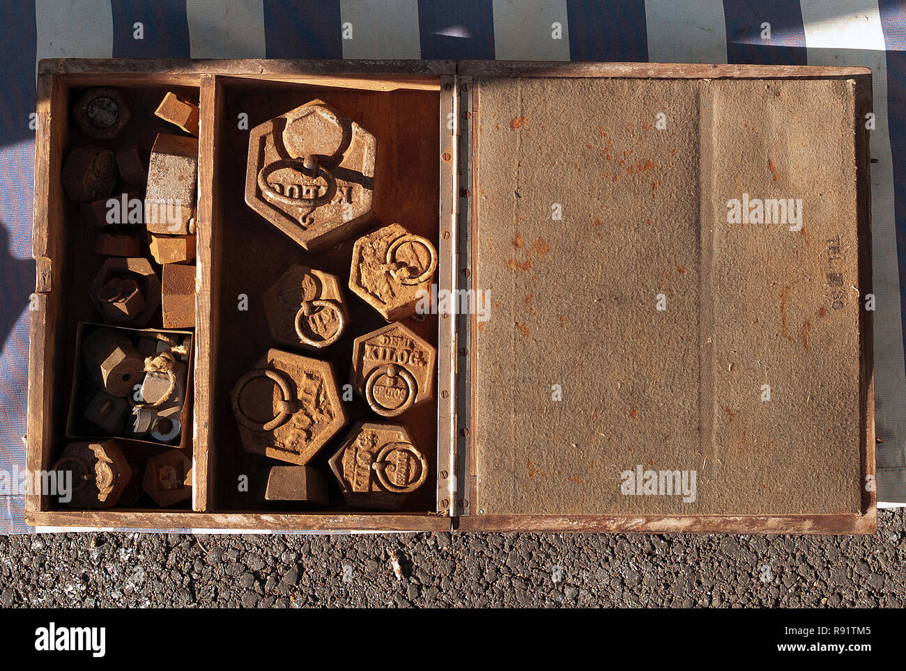 Antique weights in box at flea market, Cazals, France - Stock Image
