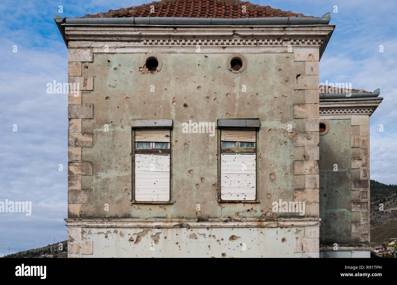 Abandoned building of Mostar still showing marks of the Bosnian war 20 years later with shrapnel and bullets holes on the faded facade - Stock Image