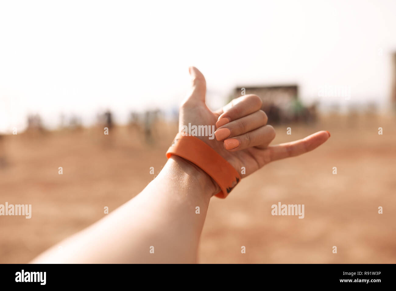 "Outdoor picture of the ""shaka"" sign is a common greeting in the Hawaiian culture, subsequently also used in surfer culture. Woman's hand on the beach Stock Photo"