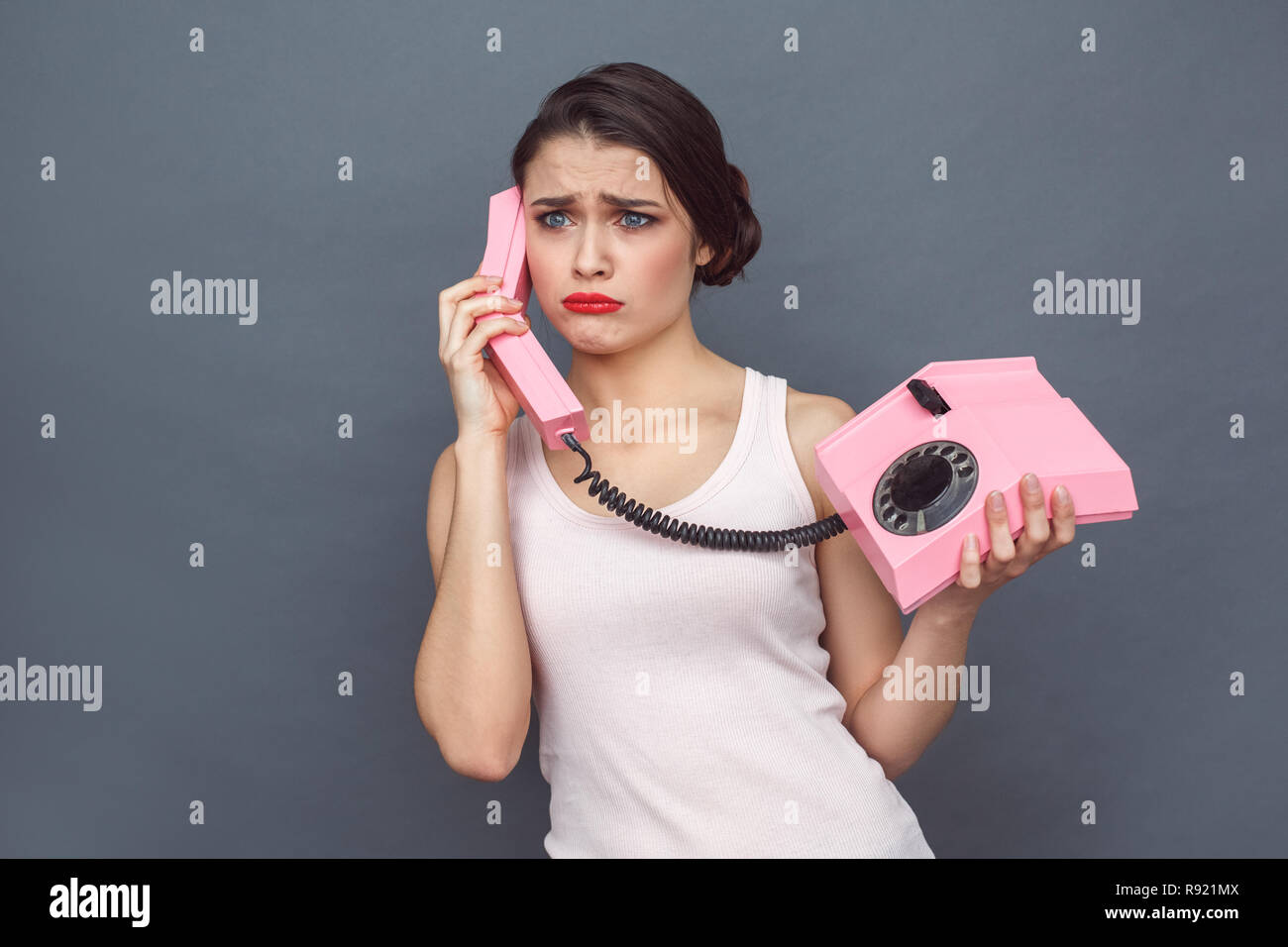 Young woman standing isolated on grey wall holding stationary phone headset talking with boyfriend grimacing upset - Stock Image