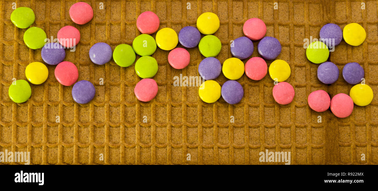 Multi-coloured chocolate M&M buttons spelling out X-mas on gingerbread house roof - Stock Image