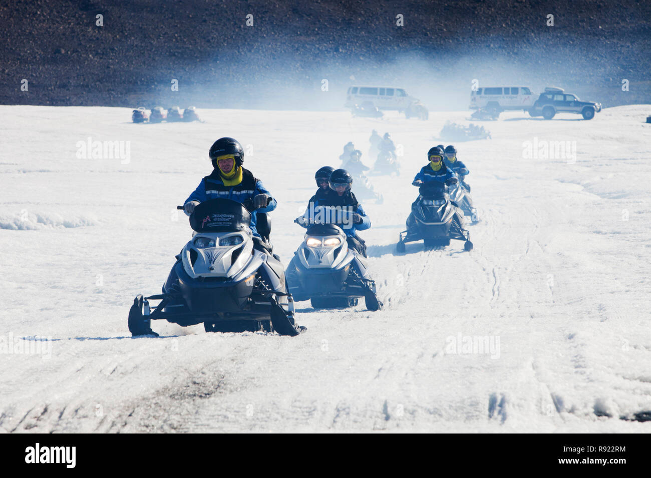 Tourists riding through a stinking fog of exhaust fumes from skidoos on the Langjokull ice sheet in Iceland. Like all of Iceland's glaciers it is retreating rapidly due to climate change. Scientists predict that all Icelands glaciers will be gone within 100 years. It is rather ironic that the tour guide mentioned  they have to drive further to reach the ice sheet every year. - Stock Image