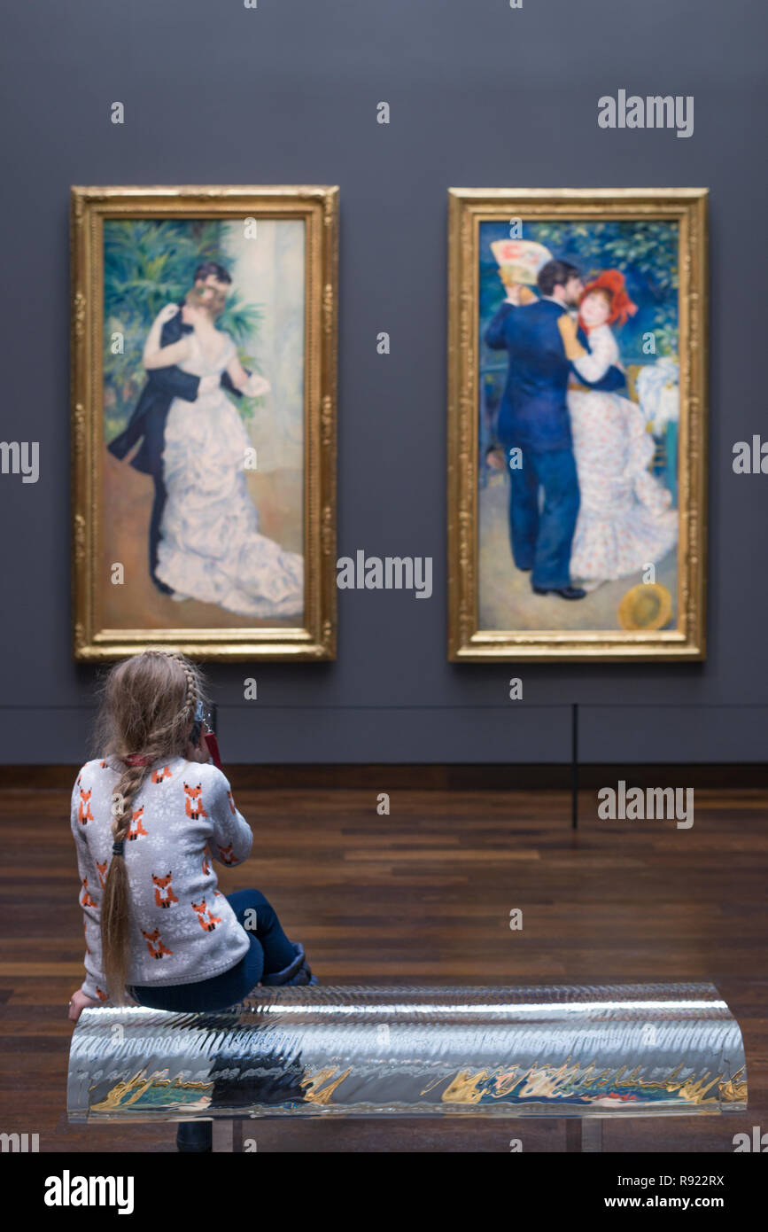 Girl seated on a bench at Musee D'Orsay in front of  'Danse a la ville' (left) and 'Danse a la campagne' (right) both by Pierre August Renoir. Musee D - Stock Image