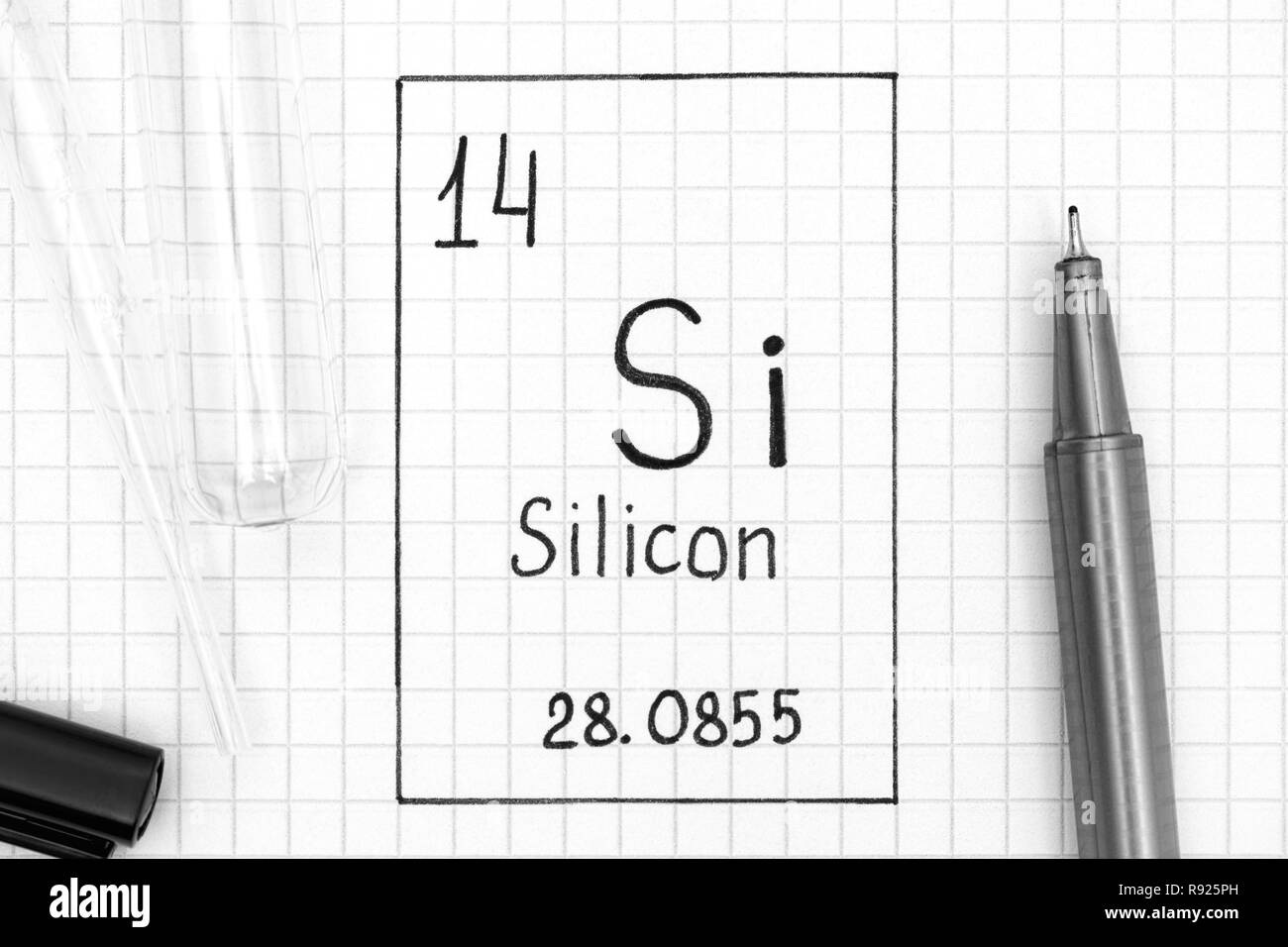 The Periodic table of elements. Handwriting chemical element Silicon Si with black pen, test tube and pipette. Close-up. Stock Photo