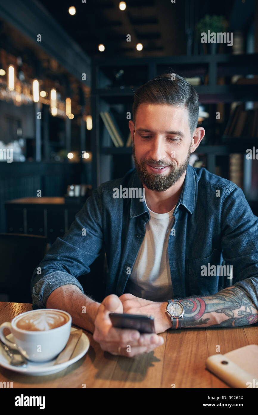 Young bearded businessman,dressed in a denim shirt, sitting at table in cafe and use smartphone. Man using gadget. Stock Photo