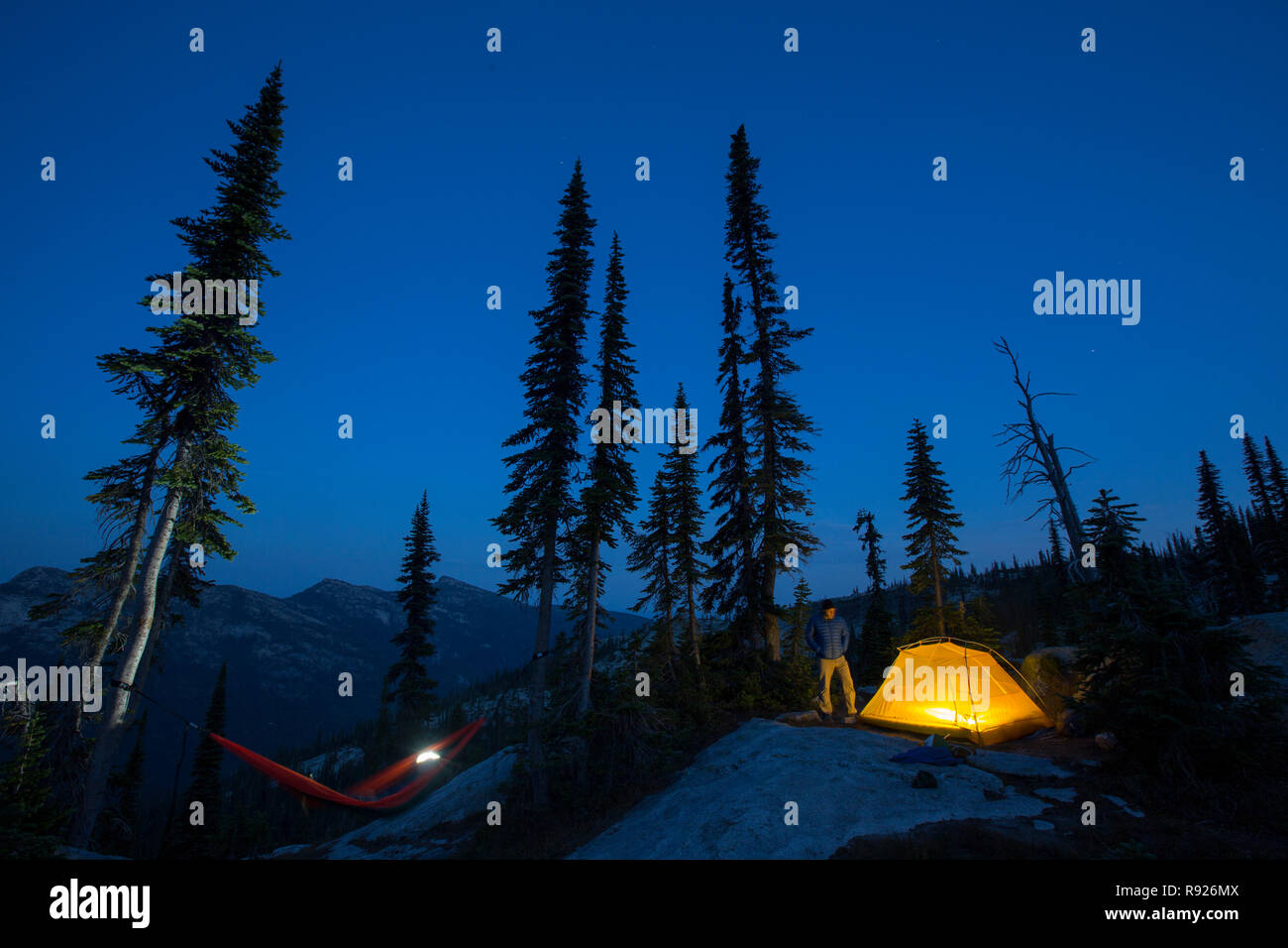 Man near a camping tent in a natural setting at night, Selkirk Mountains, Sandpoint, Idaho, USA - Stock Image