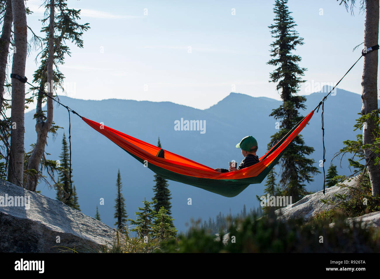 View of a boy relaxing while lying in a hammock in the mountains, Selkirk Mountains, Sandpoint, Idaho, USA - Stock Image
