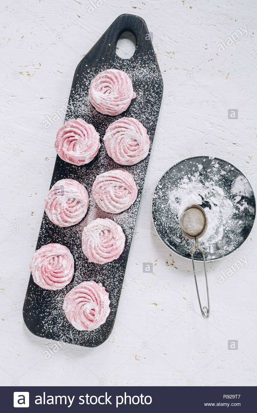 Meringue cookies dusted with sugar on a dark wood slab - Stock Image