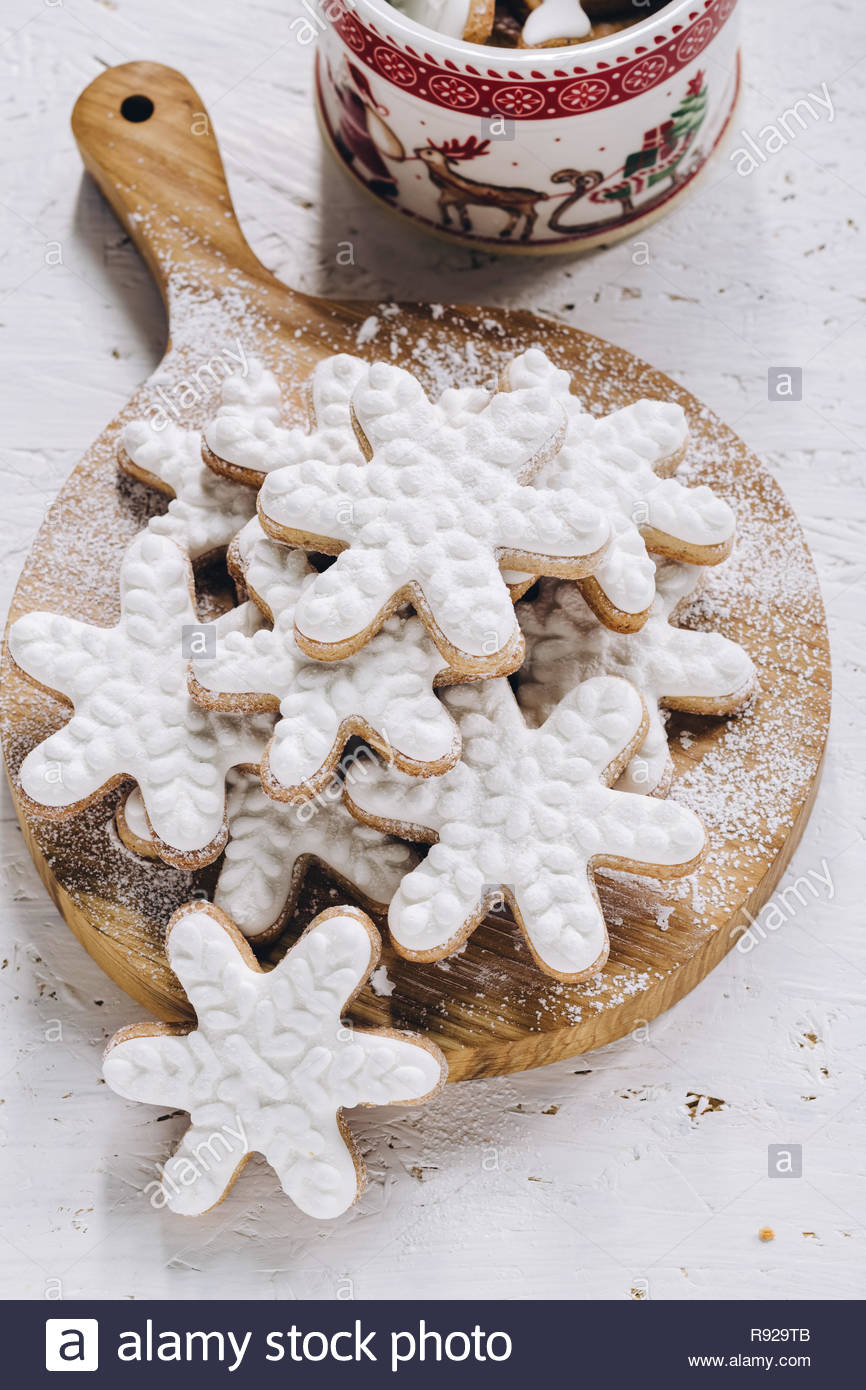 Iced snowflake cookies on a round wooden slab dusted with sugar. Close up - Stock Image