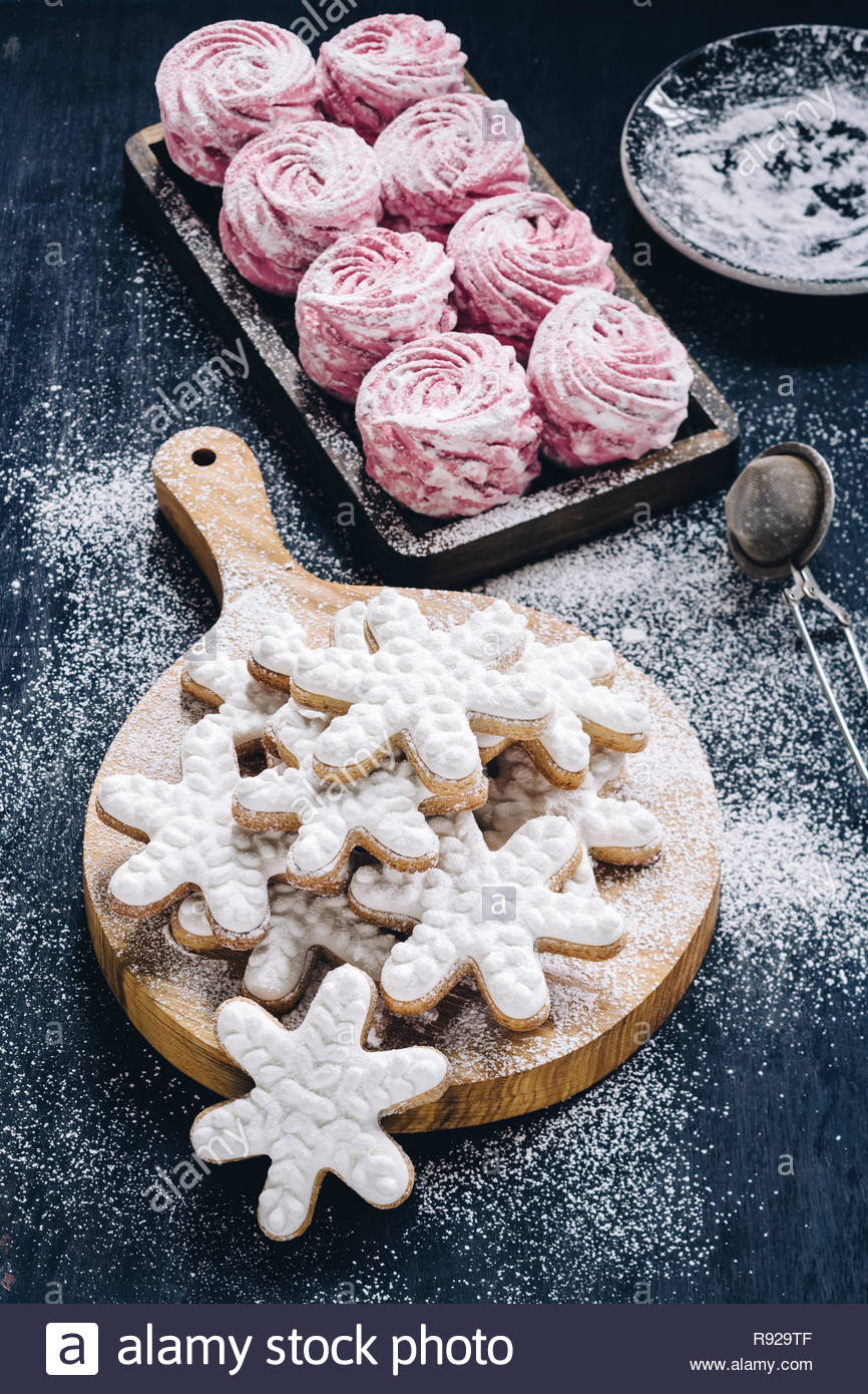 Frosted snowflake cookies and meringue cookies dusted with sugar on dark background - Stock Image