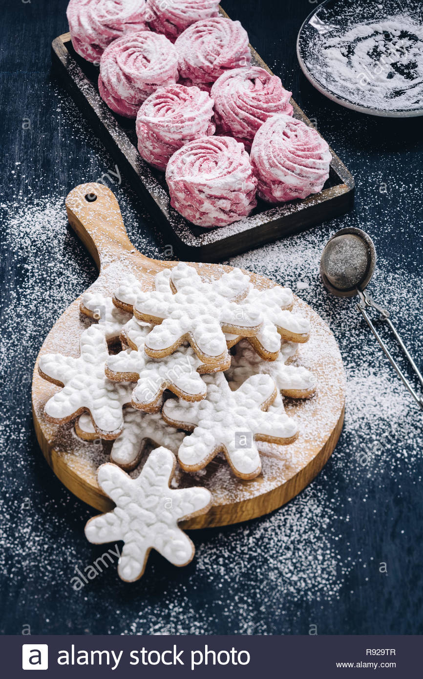 Frosted snowflake cookies and meringue cookies dusted with sugar. Vertical shot - Stock Image